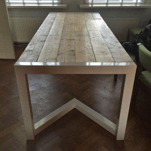 Eettafel van oude balken met een stalen punt onderstel